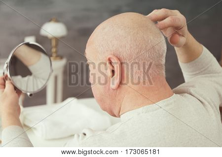 Senior bald man looking in mirror at home