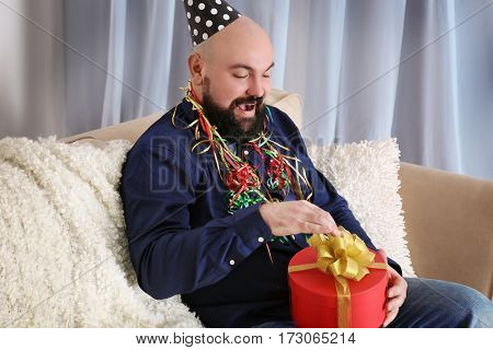 Funny fat man with birthday present sitting on sofa at home