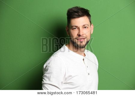 Handsome young man posing on color background