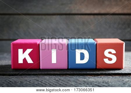 Colorful cubes with word KIDS on wooden background