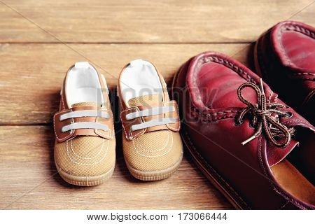 Shoes for father and son on wooden background