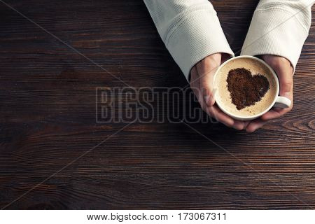 Male hands holding cup of coffee on wooden background