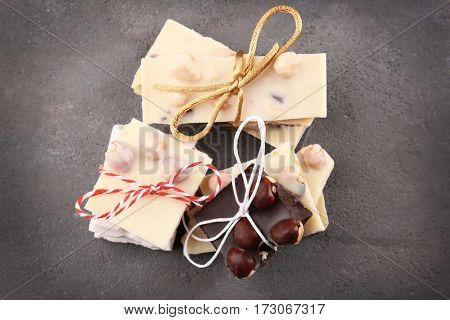 Chocolate pieces with nuts on grey background