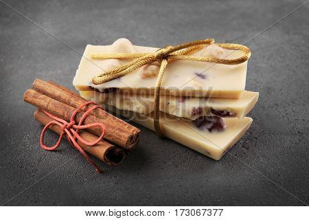 Chocolate pieces with tied cinnamon sticks on grey background