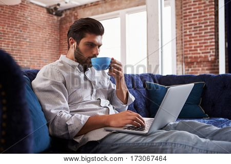 Businessman Working And Drinking Coffee On Sofa In Office