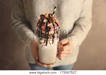 Girl holding milkshake with donuts and other sweets in jar