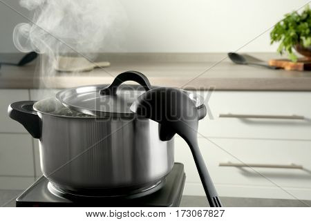 Metal saucepan with boiling water on electric stove in kitchen