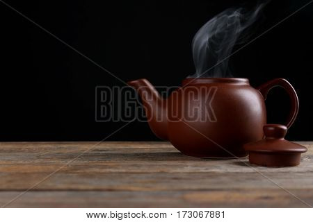 Brown kettle  with steam on dark background