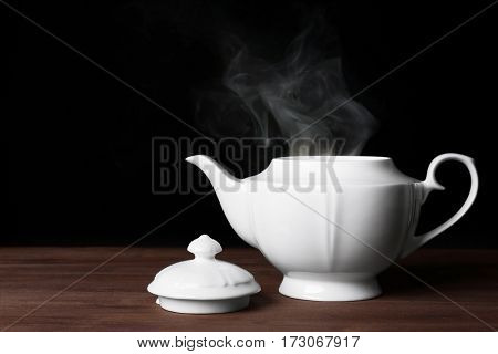 Teapot with hot water on dark background