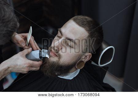 Young Bearded Man Getting Beard Haircut By Barber. Barbershop Theme