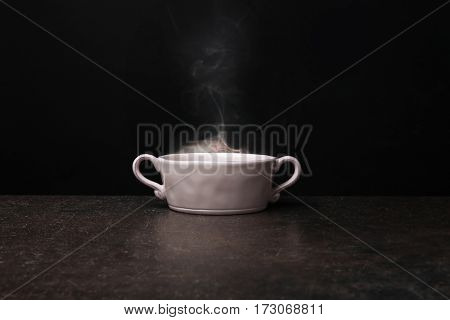 Bowl with hot water on dark background