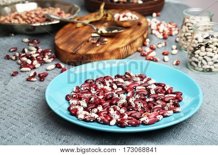 Blue plate with dried haricot beans on table