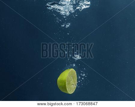 Half of fresh juicy lime falling in water on dark background