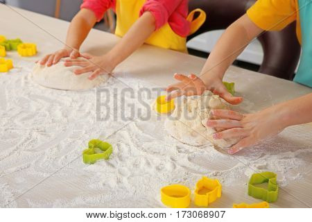 Little children making dough for Easter cookies, closeup