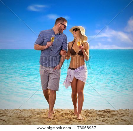 Young couple walking on tropical beach drinking champagne.