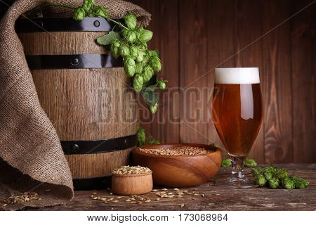 Old barrel, glass of dark beer and its ingredients on table against blurred wooden background