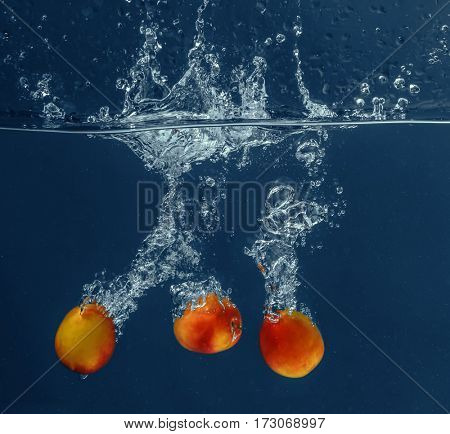 Fresh apricots falling in water on dark background
