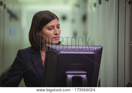 Technician working on personal computer while analyzing server in server room