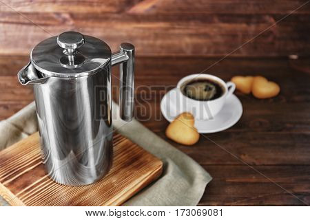 New coffee maker and cup of fresh drink with cookies on wooden background