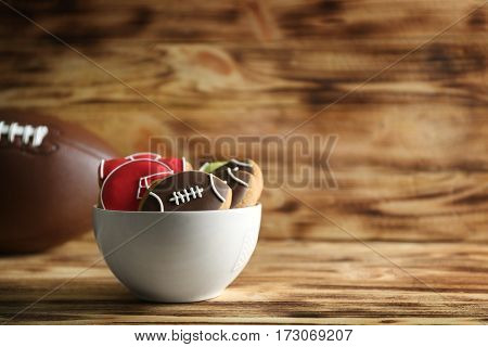 Bowl with creative cookies decorated in football style on wooden background