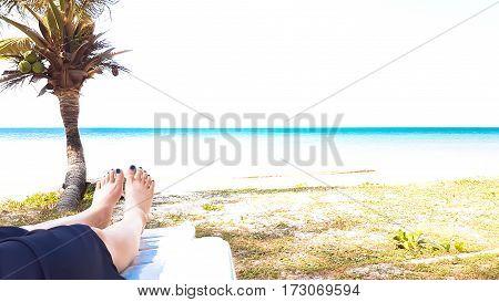 Girl's Leg Lay On White Armchair In The Beach