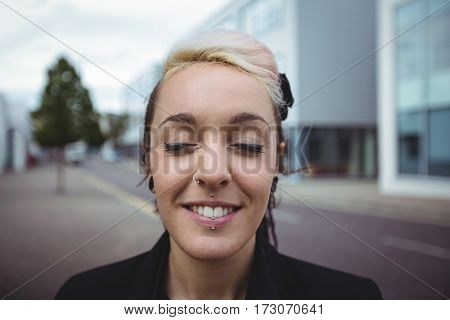 Businesswoman standing with eyes closed in office campus