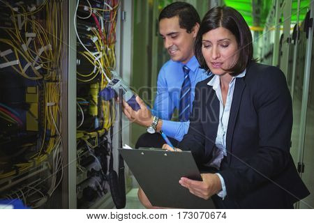Technicians analyzing rack mounted server in server room