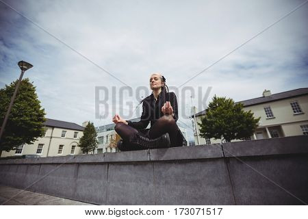 Businesswoman practicing yoga in office campus