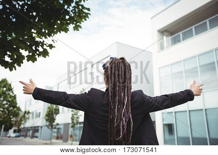 Businesswoman standing with arms outstretched in office campus