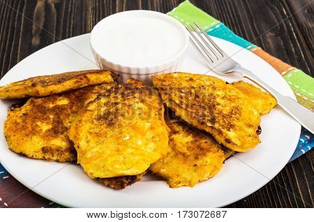 Vegetable fritters with sour cream. Studio Photo