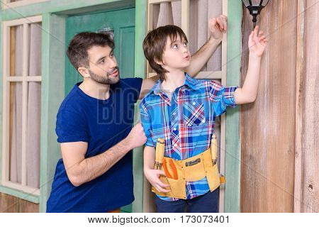 Pensive father and son in tool belt standing together and looking away on porch