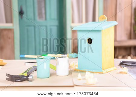 Close-up view of handmade small birdhouse with paints and tools on table