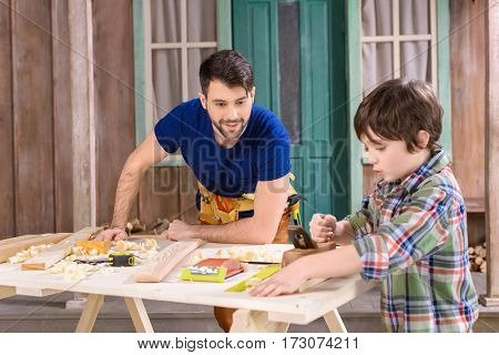 Smiling father looking at son planing wooden plank with hand plane