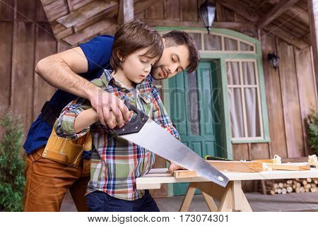 Low angle view of father teaching pensive son to saw wood in workshop