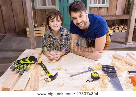 Happy father and son leaning on table with tools and smiling at camera
