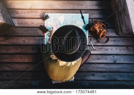 Top view of woman wearing hat looking at the world map. Tourist sitting on wooden floor exploring the world map.