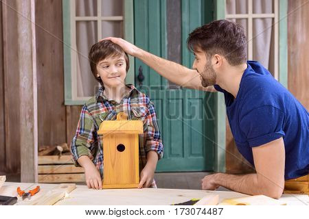 Happy father and smiling son with wooden birdhouse looking at each other in workshop