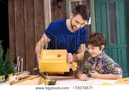 Happy father and son making wooden birdhouse together in workshop