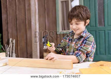Cute smiling boy in checkered shirt hammering nail in wooden plank