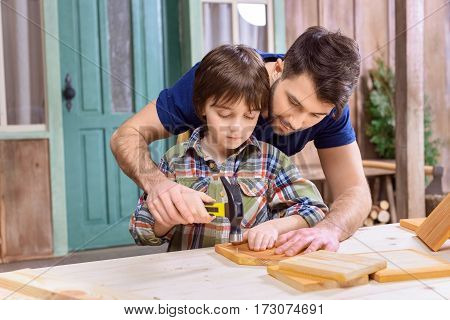 Smiling father teaching concentrated son to hammering nail in wooden plank