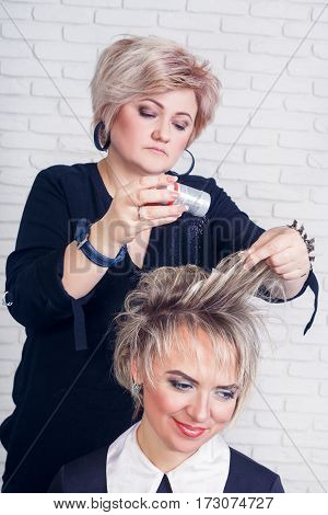 Hairdresser makes hairstyle for short hair at salon. Stylist using powder for create volume at the hair roots on client's hairstyle. Professional hairdresser middle aged woman working