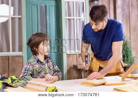 portrait of father teaching concentrated son how to hammering nail in wooden plank