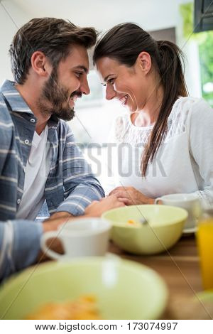 Romantic couple looking face to face while having breakfast at home