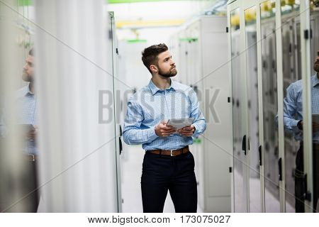 Technician using digital tablet in server room