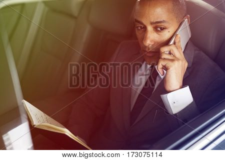 Businessman talking phone in the car