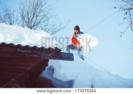 Happy young man shovelling snow against blue sky