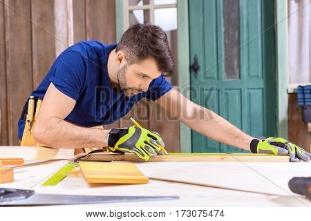 side view of concentrated carpenter in protective gloves taking measures of wooden plank
