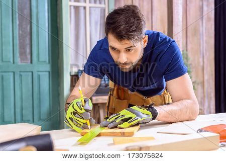 portrait of concentrated carpenter taking measures of wooden plank