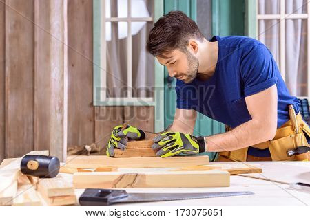 side view of carpenter in protective gloves using hand plane for shaping wood on porch