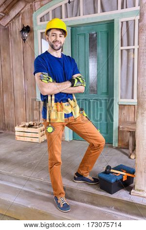smiling carpenter in helmet with building tools standing on porch and looking to camera